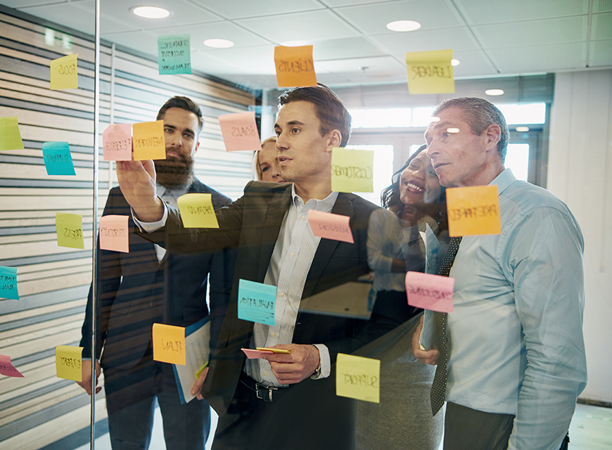 Group of business people brainstorming with sticky notes on glass window